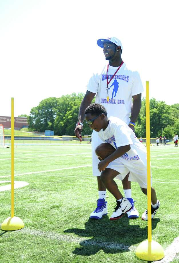 Former Husky and current Buffalo Bills wide receiver Marcus Easley coaches nine-year-old Amari Brantley, of Waterbury, during his 2nd Annual E.A.S.Y (Excellence, Achievement, Striving, Youthful) Summer Camp, a one-day football camp for children 6-15 years old, at Bunnell High School in Stratford Saturday, June 30, 2012. Photo: Autumn Driscoll / Connecticut Post