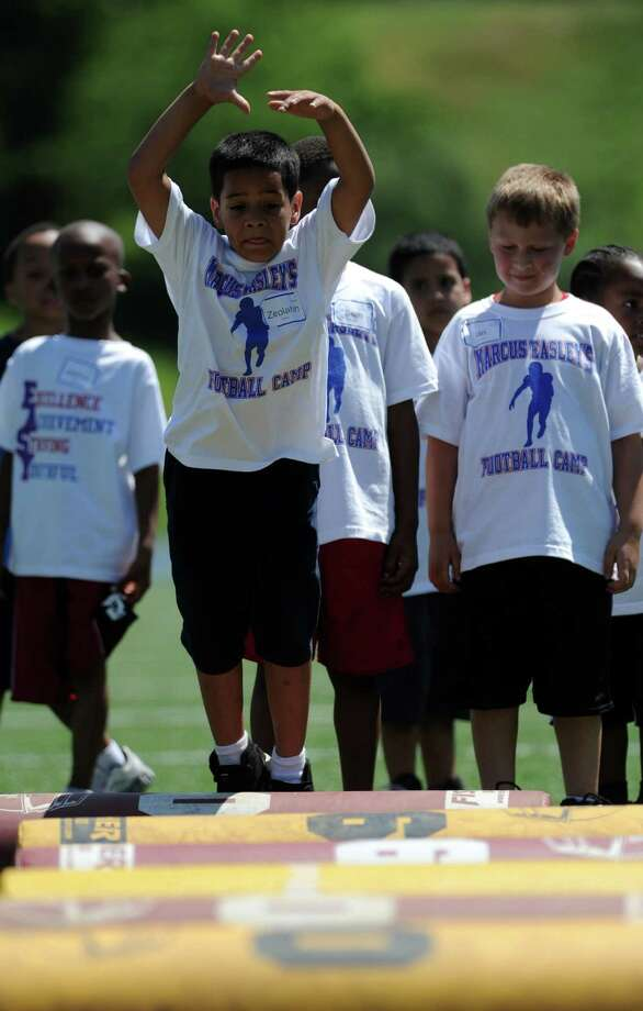 Seven-year-old Zeolahn Flores, of Bridgeport, runs through a drill during Marcus Easley's 2nd Annual E.A.S.Y (Excellence, Achievement, Striving, Youthful) Summer Camp, a one-day football camp for children 6-15 years old, at Bunnell High School in Stratford Saturday, June 30, 2012. Photo: Autumn Driscoll / Connecticut Post