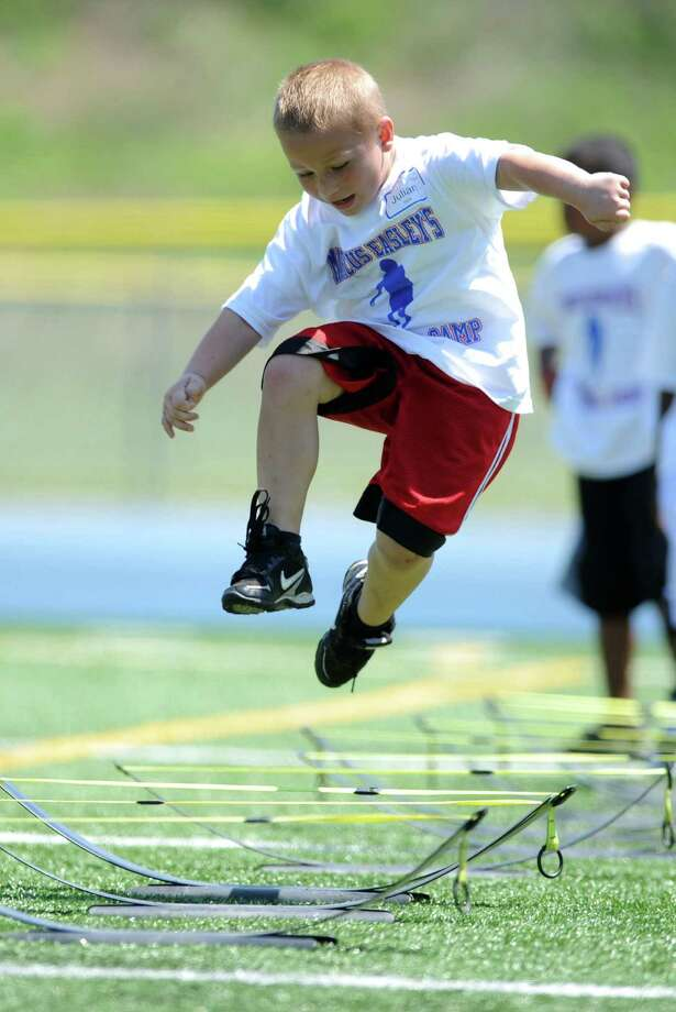 Seven-year-old Julian Basta, of Stratford, runs through a drill during Marcus Easley's 2nd Annual E.A.S.Y (Excellence, Achievement, Striving, Youthful) Summer Camp, a one-day football camp for children 6-15 years old, at Bunnell High School in Stratford Saturday, June 30, 2012. Photo: Autumn Driscoll / Connecticut Post
