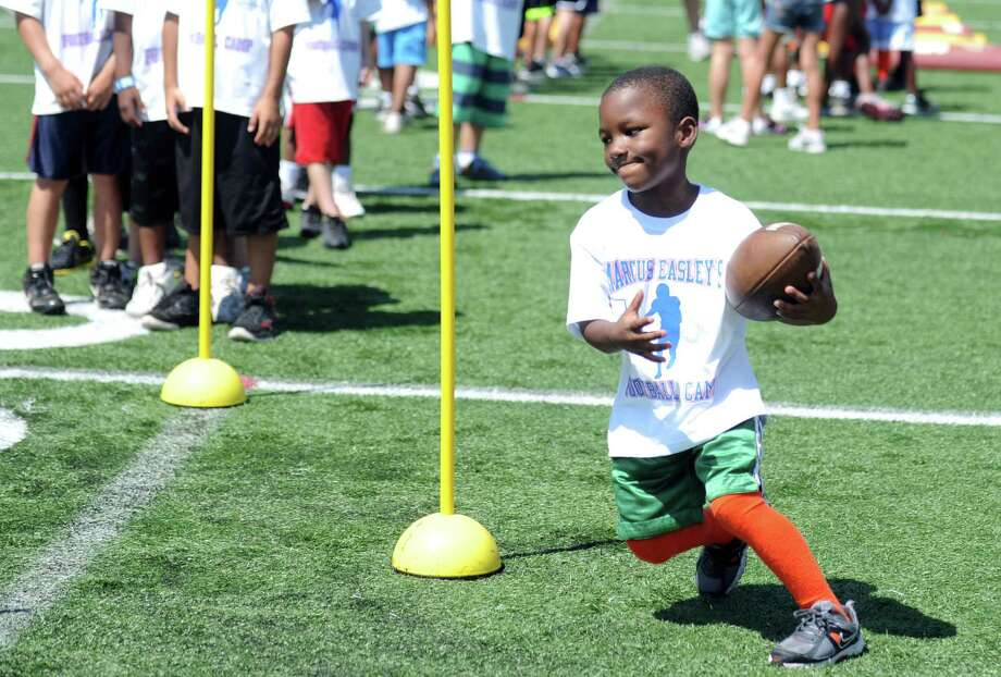 Six-year-old Christian Walters, of Hartford, runs through a drill during Marcus Easley's 2nd Annual E.A.S.Y (Excellence, Achievement, Striving, Youthful) Summer Camp, a one-day football camp for children 6-15 years old, at Bunnell High School in Stratford Saturday, June 30, 2012. Photo: Autumn Driscoll / Connecticut Post