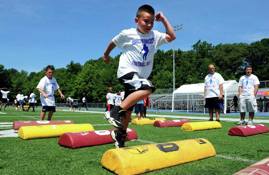 Seven-year-old Jayden Rivera, of Ansonia, runs through a drill during Marcus Easley's 2nd Annual E.A.S.Y (Excellence, Achievement, Striving, Youthful) Summer Camp, a one-day football camp for children 6-15 years old, at Bunnell High School in Stratford Saturday, June 30, 2012. Photo: Autumn Driscoll / Connecticut Post