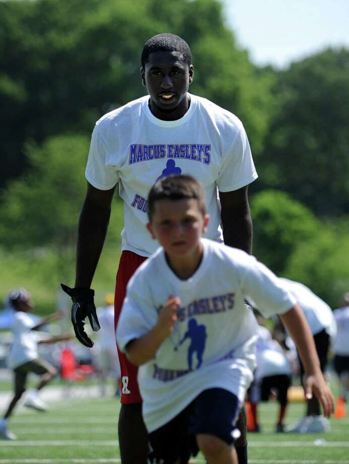 Bunnell graduate and Rutgers wide receiver Mark Harrison coaches during Marcus Easley's 2nd Annual E.A.S.Y (Excellence, Achievement, Striving, Youthful) Summer Camp, a one-day football camp for children 6-15 years old, at Bunnell High School in Stratford Saturday, June 30, 2012. Photo: Autumn Driscoll / Connecticut Post