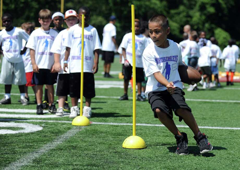 Eight-year-old Jamesyn Brothers, of Milford, runs through a drill during Marcus Easley's 2nd Annual E.A.S.Y (Excellence, Achievement, Striving, Youthful) Summer Camp, a one-day football camp for children 6-15 years old, at Bunnell High School in Stratford Saturday, June 30, 2012. Photo: Autumn Driscoll / Connecticut Post