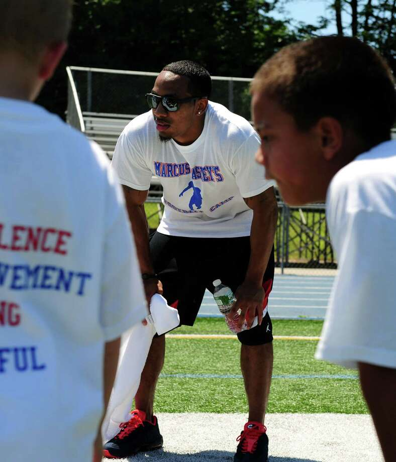 Former Husky and current Cincinnati Bengals wide receiver Kashif Moore coaches during Marcus Easley's 2nd Annual E.A.S.Y (Excellence, Achievement, Striving, Youthful) Summer Camp, a one-day football camp for children 6-15 years old, at Bunnell High School in Stratford Saturday, June 30, 2012. Photo: Autumn Driscoll / Connecticut Post