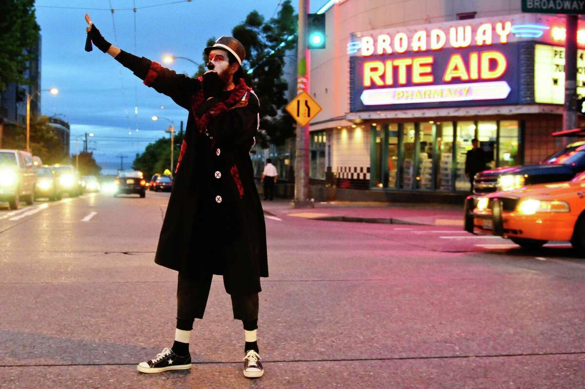 A member of the Clandestine Insurgent Rebel Clown Army directs traffic with a whistle on Broadway in Seattle on Friday, June 29, 2012, during a protest of police actions during a Pride weekend