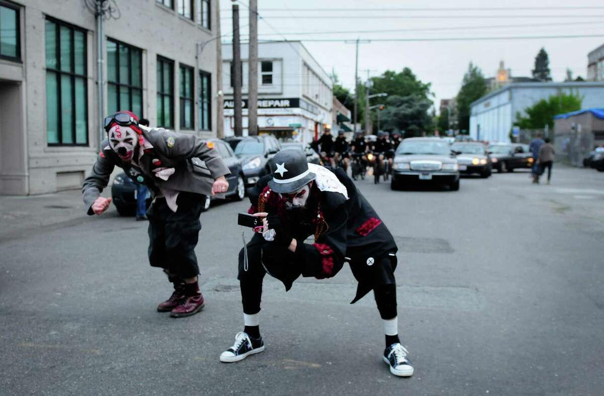 Two members of the Clandestine Insurgent Rebel Clown Army stick out their behinds to Seattle police.
