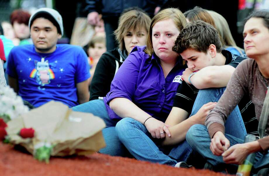 "Marley Blonsky, center, becomes emotional as she holds Whitney Young, right center, during a vigil for Mollie Olgin, 19, and Mary Chapa, 18, at Cal Anderson Park in Seattle on Friday, June 29, 2012. Both Portland, Texas women were found shot in the head on June 23. Olgin died from her wounds, but Chapa is currently recovering in a local hospital. AP reports: ""Police describe the suspected gunman as a 5-foot-8-inch, 140-pound white male in his 20s with dark hair. Police say they haven't determined a motive, and Police Chief Randy Wright has said there's no evidence suggesting the women's relationship was involved."" Photo: LINDSEY WASSON / SEATTLEPI.COM"