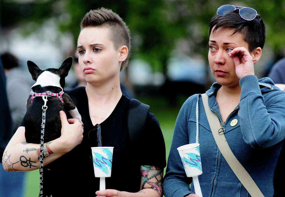 Daly Mellinger holds Norma Jean, a Boston Chihuaha, as she watches the vigil with Jennifer Cota.