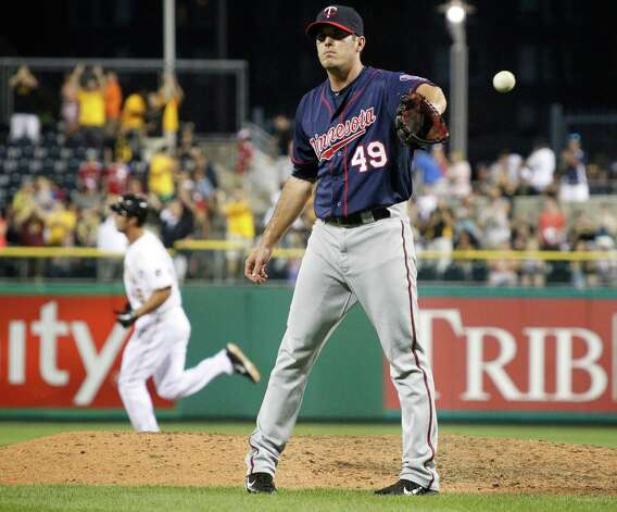 Minnesota Twins relief pitcher Jeff Manship (49) gets a new ball as Pittsburgh Pirates' Garrett Jones rounds the bases after hitting a two-run home run in the seventh inning of the baseball game on Thursday, June 21, 2012, in Pittsburgh. The Pirates won 9-1. Photo: AP
