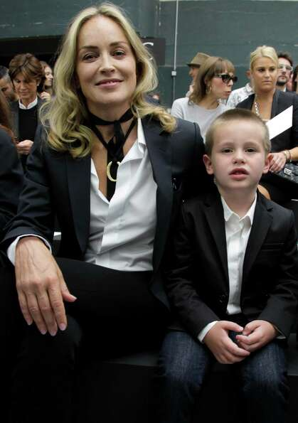 Sharon Stone and her son Quinn Kelly Stone attend the show of Belgian fashion designer Kris Van Assc