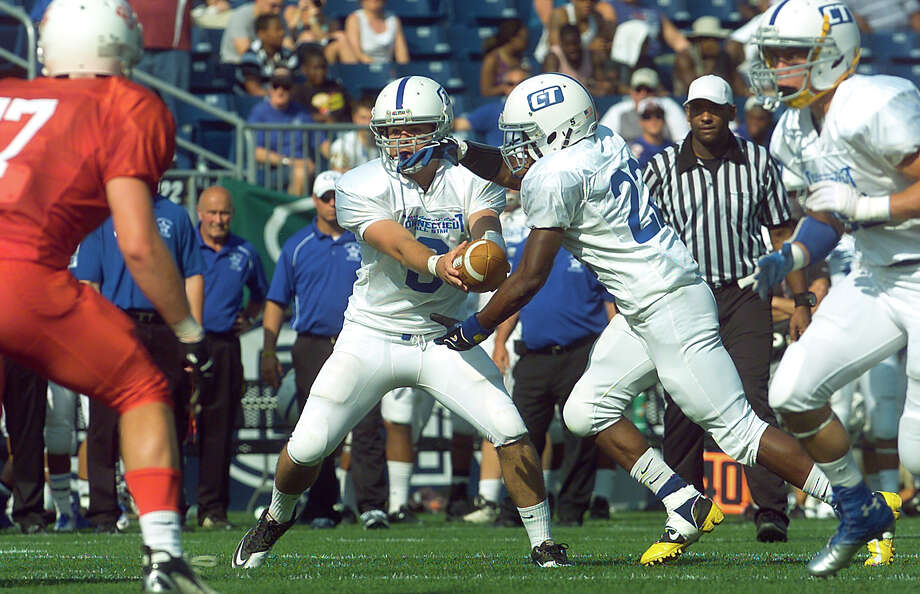 Connecticut's #22 Leaon Gordon, of Brookfield, receives the ball from quarterback Henry Foye, during the 2012 Govenors' Cup 14th Annual Senior High School All-star Football game against Rhode Island at Rentschler Field in East Hartford, Conn. on Saturday June 30, 2012. Photo: Christian Abraham / Connecticut Post