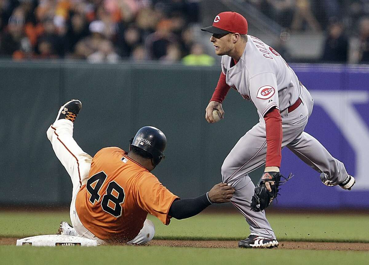 San Francisco Giants' Pablo Sandoval grabs the leg of Cincinnati Reds shortstop Zack Cozart in the fourth inning of a baseball game Friday, June 29, 2012, in San Francisco. Sandoval was called for interference on the play, and Brandon Belt was called out at first base.