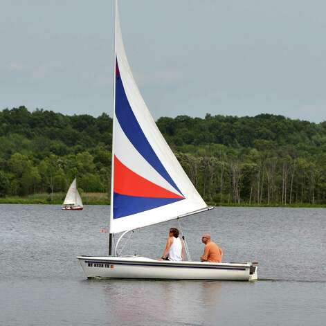 Birant Okbay,left, and his father Kunter Okbay, both of Niskayuna, sail on Round Lake Saturday June 30, 2012.   (John Carl D'Annibale / Times Union) Photo: John Carl D'Annibale