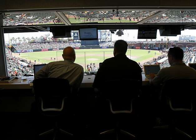 Michael Duca (left) watches a Giants game at AT&T Park from the press box in his capacity as official scorer. Photo: Brant Ward, The Chronicle