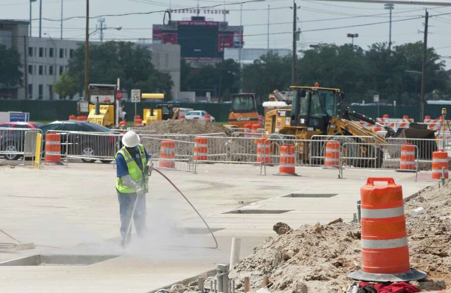 Crews work on the new light rail last week by the University of Houston central campus near Scott Street and Wheeler Avenue. Right-of-way issues have slowed the project, which is supposed to be done by 2014. Photo: Nick De La Torre / © 2012  Houston Chronicle
