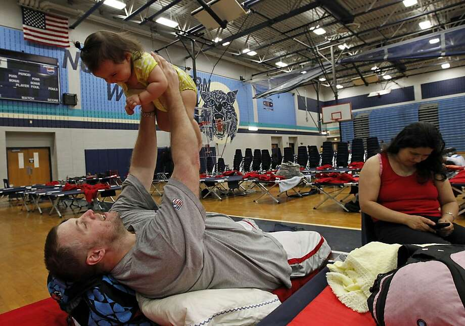 Robert St. Denny plays with his daughter, 9-month-old Lily St. Denny, as his wife Kelly Reyes sits at right, at a Red Cross shelter at Northwestern High School gym Saturday, June 30, 2012, in Hyattsville, Md. The apartment complex the St. Denny's live in was damaged by violent evening storms following a day of triple-digit temperatures that also wiped out power to more than 2 million people across the eastern United States. (AP Photo/Alex Brandon) Photo: Alex Brandon, Associated Press