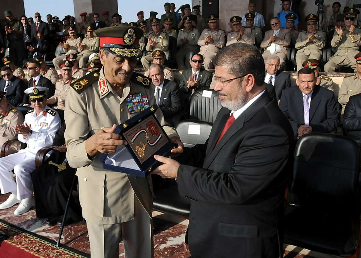 """In this handout picture made available by the Egyptian presidency on June 30, 2012, military council chief Field Marshal Hussein Tantawi (L), presents the """"shield of the Armed Forces"""" the Egyptian military's highest honor to President Mohamed Morsi (R) during a ceremony at a military base in of Cairo. Morsi was sworn in as Egypt's first freely elected civilian president on Saturday and formally received a transfer of power and pledge of support from the military, which has ruled since last year. AFP PHOTO / HO ==RESTRICTED TO EDITORIAL USE - MANDATORY CREDIT """"AFP PHOTO /EGYPTIAN PRESIDENCY """" - NO MARKETING NO ADVERTISING CAMPAIGNS - DISTRIBUTED AS A SERVICE TO CLIENTS==-/AFP/GettyImages"""