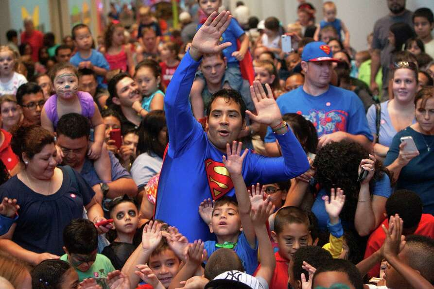 Angel Ramirez, dressed as Superman, center, leads visitors in a dance party during Superman's Birthd