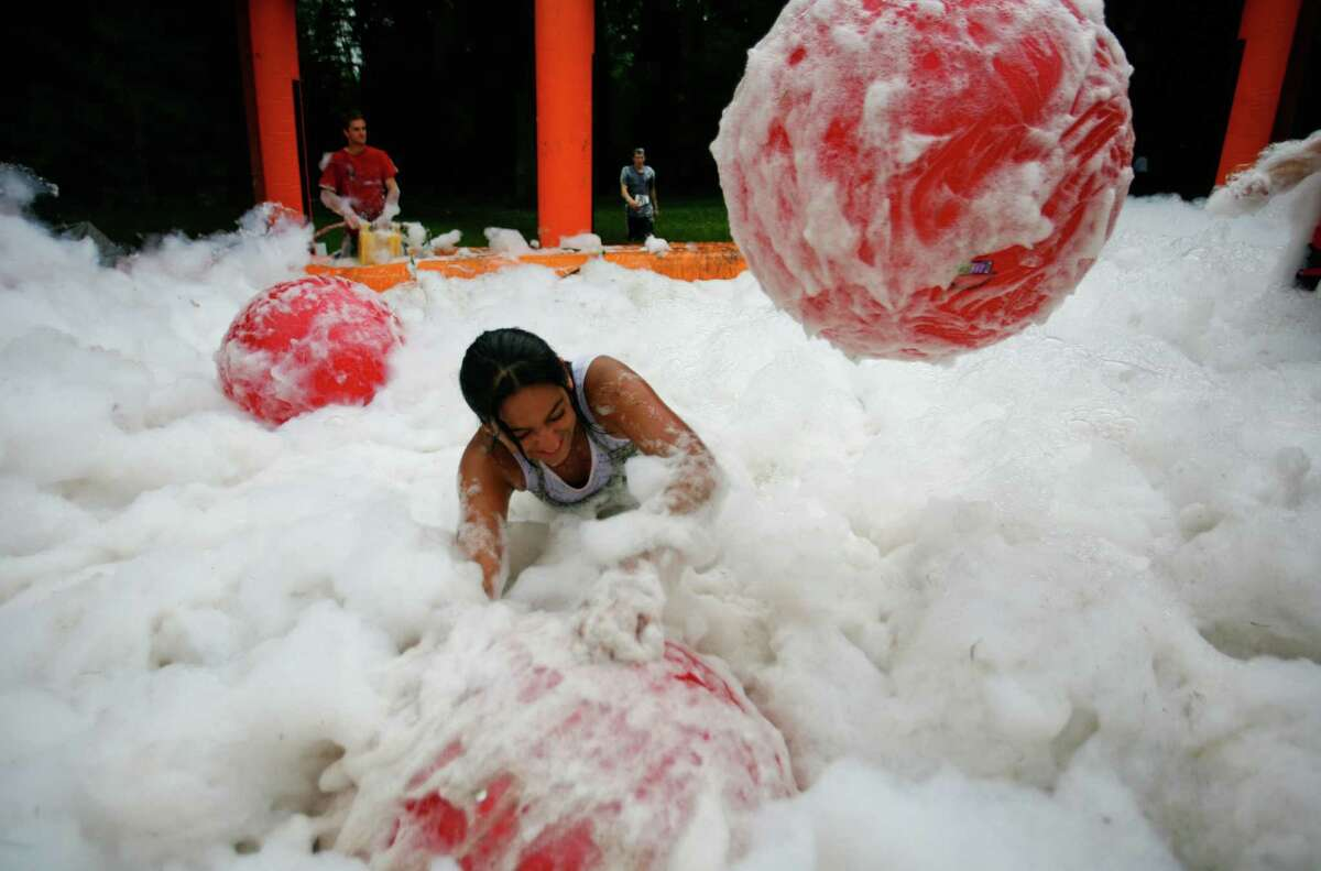A participant of the 5K Foam Fest plays in a foam pit.