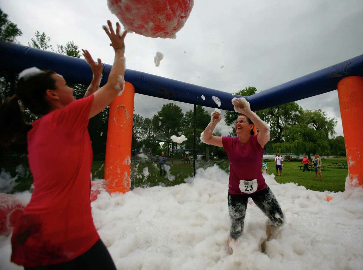 Participants of the 5K Foam Fest play in a foam pit.