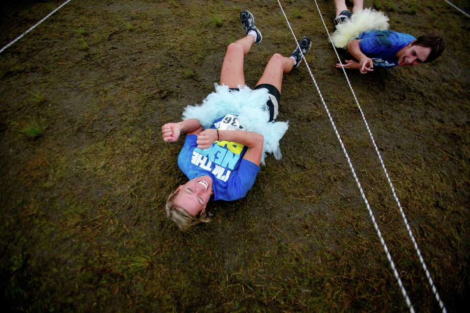 A participant of the 5K Foam Fest laughs after touching an electrial wire obstacle. Photo: SOFIA JARAMILLO / SEATTLEPI.COM