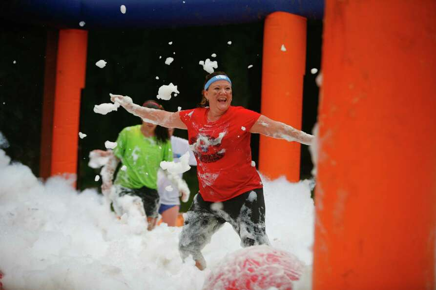 A participant of the 5K Foam Fest jumps into a foam pit.