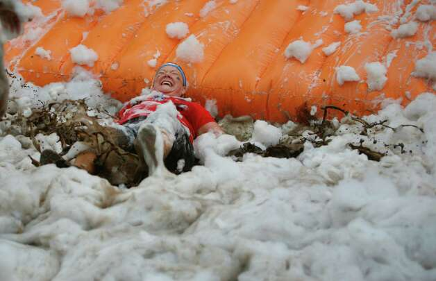 A participant of the 5K Foam Fest lands in a puddle of mud and foam. Photo: SOFIA JARAMILLO / SEATTLEPI.COM
