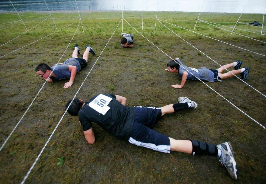 Participants of the 5K Foam Fest crawl under an electrical wire obstacle. Photo: SOFIA JARAMILLO / SEATTLEPI.COM