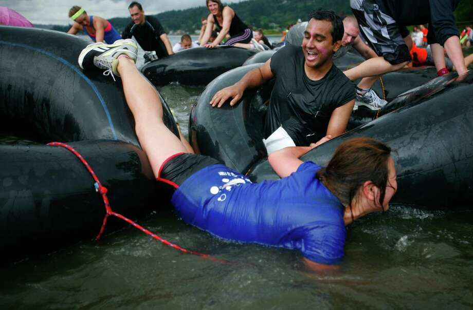 Participants of the 5K Foam Fest crawl across an innertube obstacle. Photo: SOFIA JARAMILLO / SEATTLEPI.COM