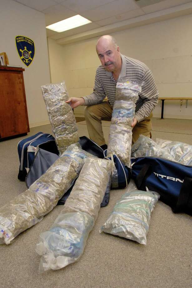John Burke of the Albany County Sheriff's Office displays marijuana grown in Canada and shipped into New York state. The drugs were confiscated from a man and woman traveling south on Interstate 87 in 2008. (Paul Buckowski / Times Union) Photo: Paul Buckowski / Albany Times Union