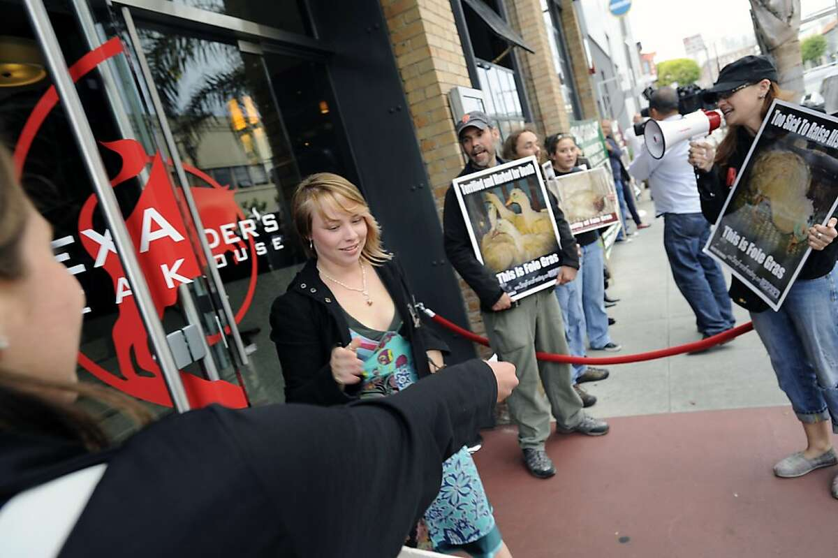 Customer Sarah Jones of San Francisco takes a flier from a protester in front of Alexander's Steakhouse. Alexander's Steakhouse held their last farewell to foie gras dinner and fundraiser in San Francisco, CA Saturday June 30th, 2012.