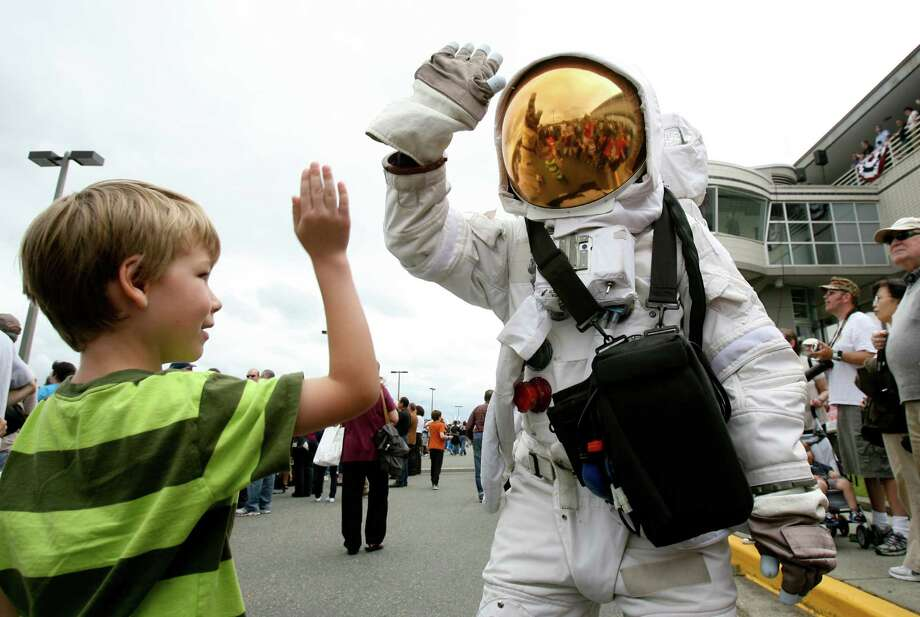 Henry Bevil, 6, high-fives a space-suited person during the arrival of the Space Shuttle Trainer Crew Compartment in NASA's Super Guppy aircraft at the Museum of Flight in this file photo from June 30, 2012. Boeing debuted its newest space suit on Wednesday which is a much lighter design that past suits. Scroll through the slideshow to see NASA's space suits throughout the years. Photo: LINDSEY WASSON / SEATTLEPI.COM