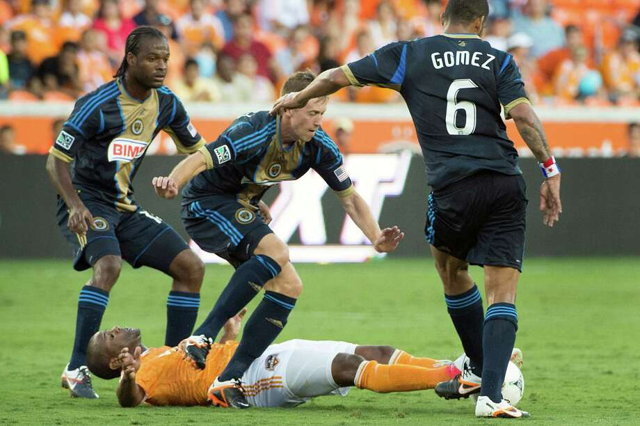 Luiz Camargo hits the turf under Brian Carroll during the first half. Photo: Smiley N. Pool, Houston Chronicle / © 2012  Houston Chronicle