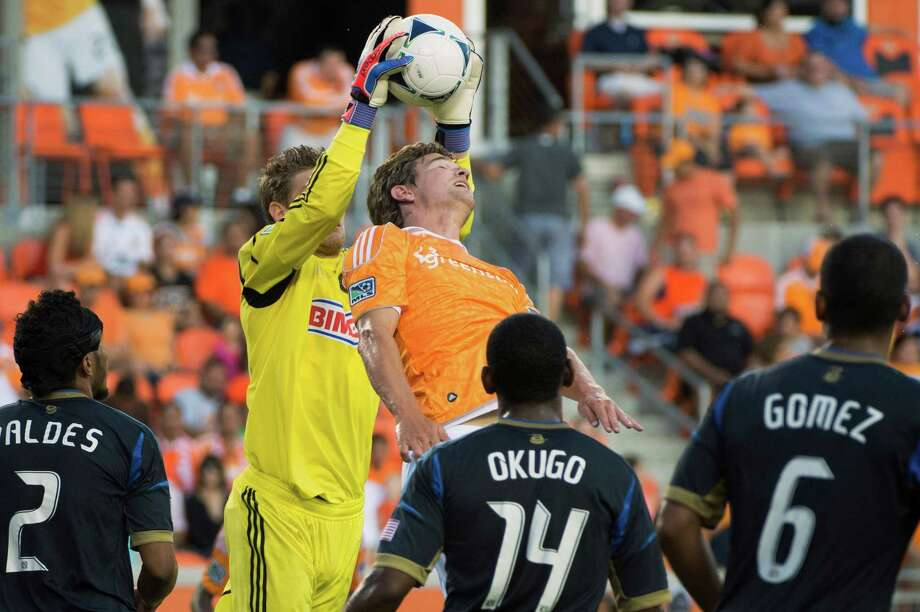 Zac MacMath  takes a ball away from Bobby Boswell. Photo: Smiley N. Pool, Houston Chronicle / © 2012  Houston Chronicle