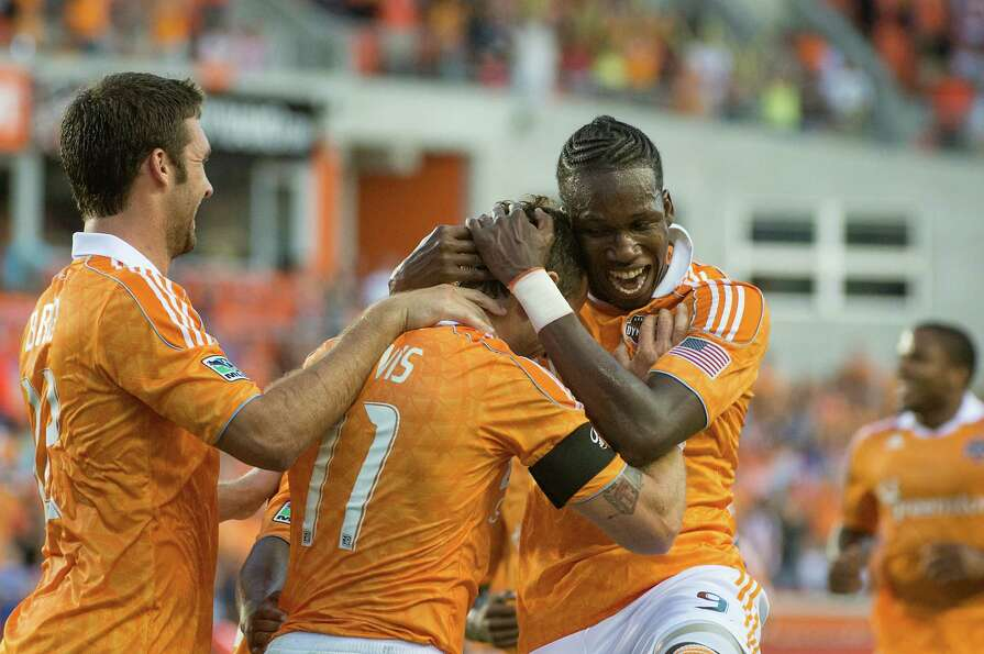 Macoumba Kandji leaps on Brad Davis after Davis scored during the first half.