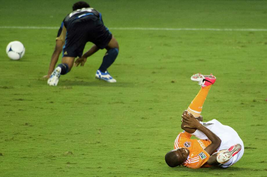 Boniek Garcia tumbles to the turf after a collision with Amobi Okugo (during the second half. Photo: Smiley N. Pool, Houston Chronicle / © 2012  Houston Chronicle