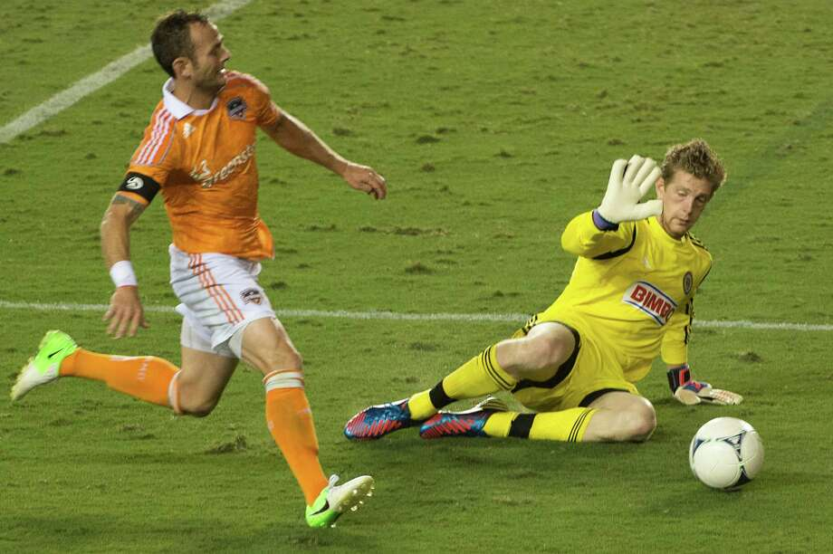 Zac MacMath makes a stop on Brad Davis during the second half. Photo: Smiley N. Pool, Houston Chronicle / © 2012  Houston Chronicle