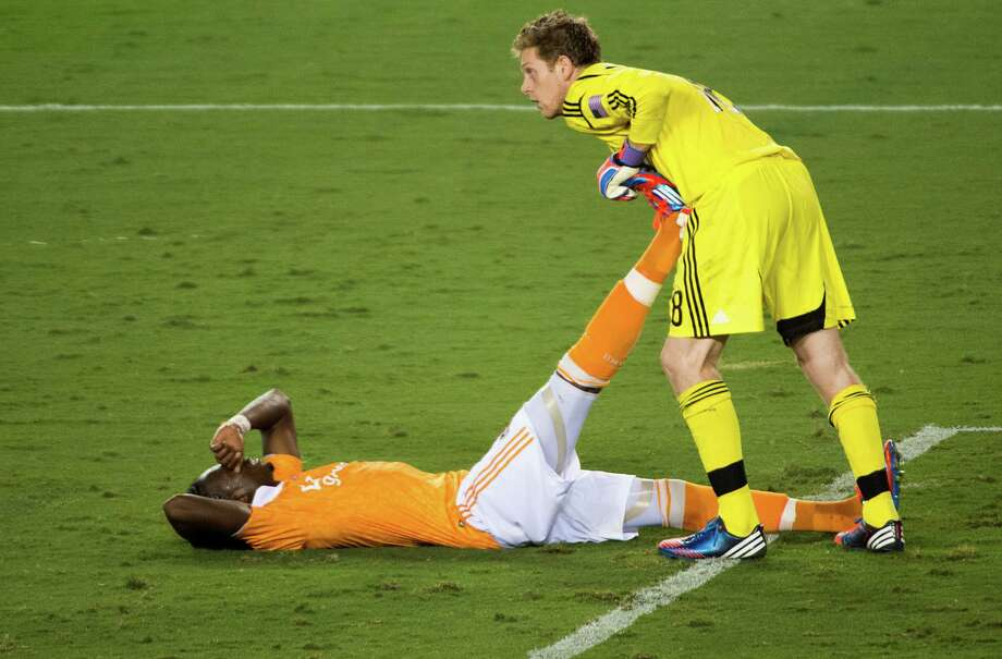 Union goalkeeper Zac MacMath helps Macoumba Kandji stretch out a cramp during the second half. Photo: Smiley N. Pool, Houston Chronicle / © 2012  Houston Chronicle