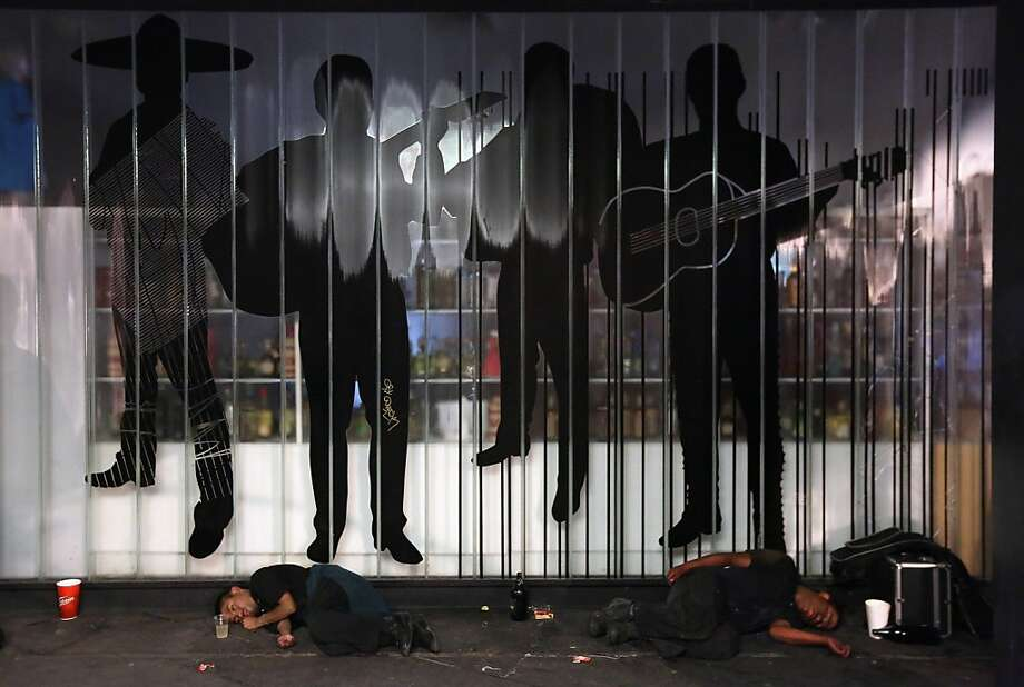 """MEXICO CITY, MEXICO - JUNE 30:  Men sleep under a mariachi mural at Garibaldi Plaza early on June 30, 2012 in Mexico City, Mexico. Revelers partied into the early hours of the morning, even as a midnight ban on the sale of alcohol went into effect. The alcohol ban, known as """"ley seca"""" is meant to curb possible violence as Mexicans go to the polls Sunday to choose a new president.  (Photo by John Moore/Getty Images) Photo: John Moore, Getty Images"""