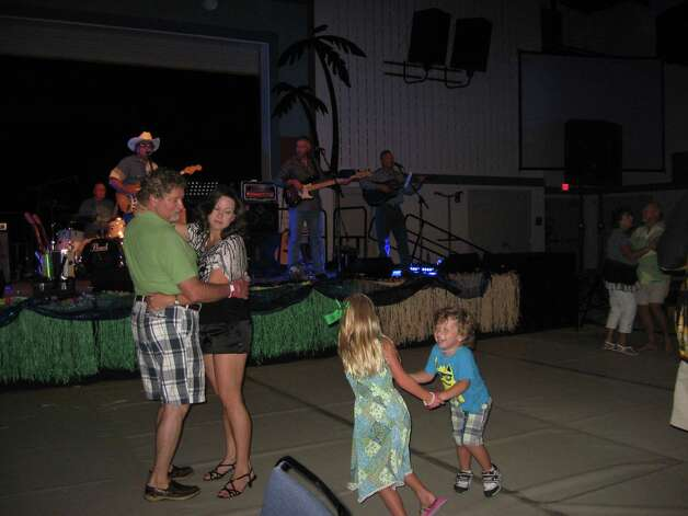 Nederland residents Ricky and Keli Lanclos dance to the music of The Classics Recovered while keeping an eye on their 3-year-old son Ryder, dancing with cousin Kamryn Brammer. Family fun was the focus of the Southern Summer Nights event Saturday night on the Lamar Port Arthur campus. Photo: Sarah Moore