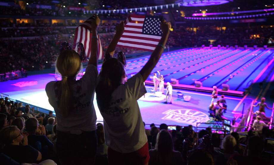 Allyson Schwarz, 13, and Hannah Truslow, 14, hold up United States flags before the swimming Olympic Trials in Omaha, Neb., Saturday, June 30, 2012. Photo: Rebecca S. Gratz, Associated Press / OMAHA WORLD-HERALD