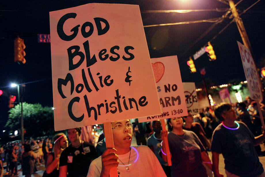 Angela Weddle carries a sign during the Pride Bigger Than Texas Parade held Saturday June 30, 2012. Mollie Judith Olgin, 19, and her girlfriend Mary Kristene Chapa, 18, were found shot in the head last Saturday in a Portland, Tx park. Olgin died at the scene and Chapa is in stable condition in the hospital. Photo: Edward A. Ornelas, San Antonio Express-News / © 2012 San Antonio Express-News