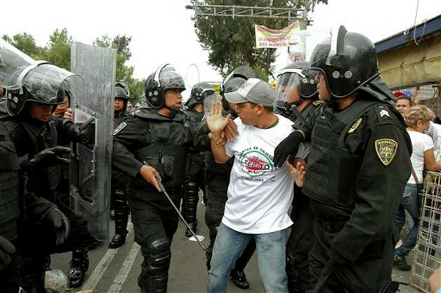 A man is taken away by riot police after residents of the Tepito neighborhood clashed with riot police in Mexico City, Wednesday June 27, 2012. According to the Mexico City Public Safety Secretary, residents took to the streets, clashed with police and several cars were burned after 4 men were arrested on suspicion of selling stolen merchandise. So far, another 19 people have been detained during the clashes with police. (AP Photo) Photo: Associated Press