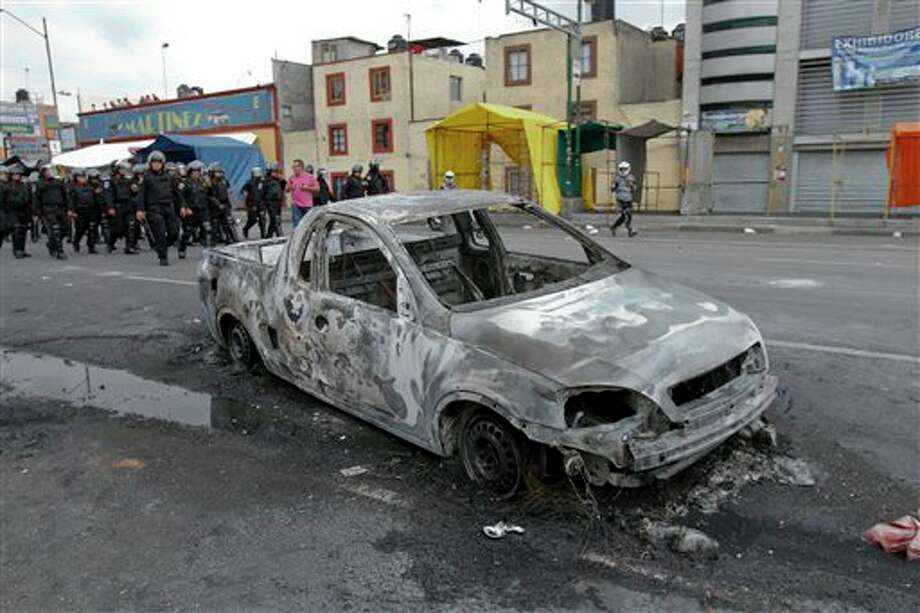 Riot police advance past a burned out vehicle after residents of the Tepito neighborhood clashed with riot police in Mexico City, Wednesday June 27, 2012. According to the Mexico City Public Safety Secretary, residents took to the streets, clashed with police and several cars were burned after 4 men were arrested on suspicion of selling stolen merchandise. So far, another 19 people have been detained during the clashes with police. (AP Photo) Photo: Associated Press