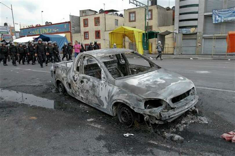 Riot police advance past a burned out vehicle after residents of the Tepito neighborhood clashed wit