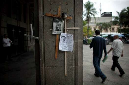 In this photo taken on Thursday, June 21, 2012, two men walk past posters of missing people attached to crosses hanging from a pillar of the governor's palace in the main square of Cuernavaca, Mexico. As Mexicans head to the ballot box Sunday, drug cartels are registering their votes with scare tactics and cold, hard cash to make sure whoever is elected doesn�t interfere with their lucrative operations. (AP Photo/Alexandre Meneghini) Photo: Associated Press
