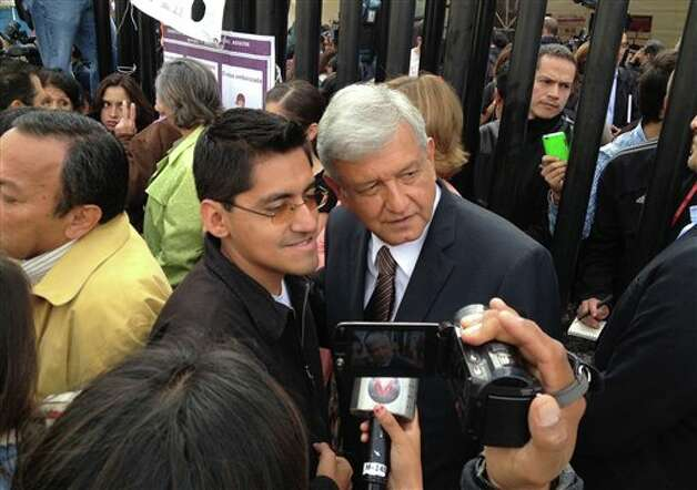 Mexican presidential candidate Andres Manuel Lopez Obrador of the Democratic Revolution Party (PRD) poses for a photo, while the candidate and others stand in line to vote at a polling station in Mexico City, Sunday, July 1, 2012. Mexico's more than 79 million voters head to the polls Sunday to elect a president, who serves one six-year term, as well as 500 congressional deputies and 128 senators. (AP Photo/Eduardo Verdugo) Photo: Associated Press