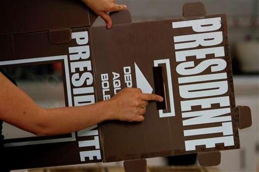 La funcionaria electoral Ninel Ram�rez Torillo muestra una urna antes de ser desdoblada que ser� usada para la elecci�n presidencial en la ciudad de M�xico, el s�bado 30 de junio de 2012. (Foto AP/Marco Ugarte) Photo: Associated Press