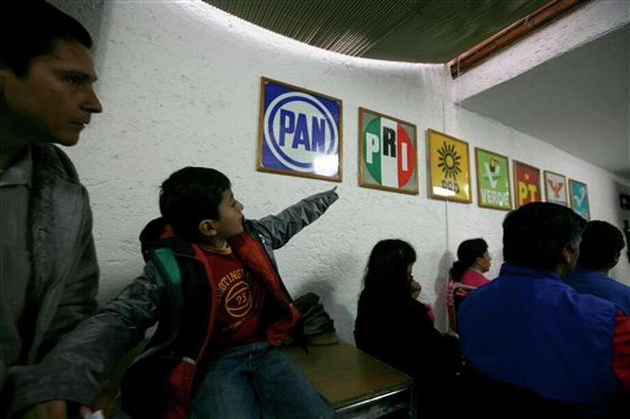Un ni�o apunta a los logotipos de los diferentes partidos pol�ticos mientras acompa�a a un adulto a una reuni�n de funcionarios electorales antes de los comicios generales de M�xico, el s�bado 30 de junio de 2012, en la ciudad de M�xico. (Foto AP/Marco Ugarte) Photo: Associated Press