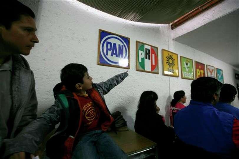 Un ni�o apunta a los logotipos de los diferentes partidos pol�ticos mientras acompa�a a un adu